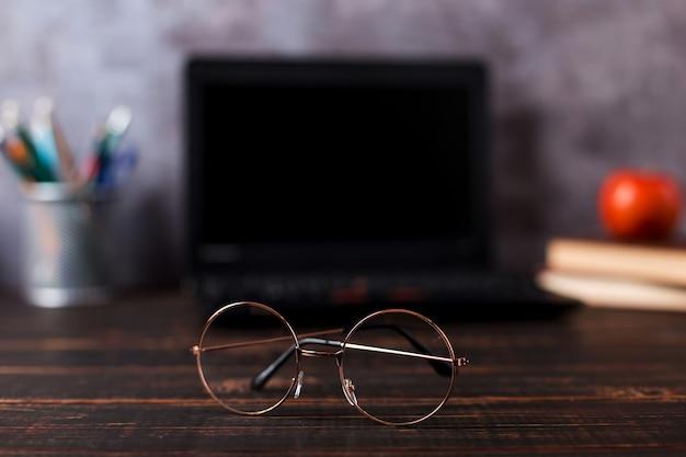 Canetas, maçã, lápis, livros, laptop e óculos em cima da mesa, no fundo do quadro-negro