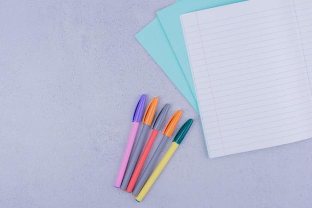 Canetas multicoloridas e um pedaço de papel em branco xadrez.
