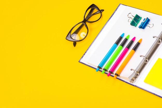 Canetas, óculos e caderno brilhantes mentem isolado em fundo amarelo