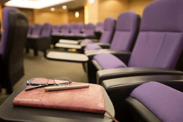 Canetas, óculos e cadernos na sala de reuniões.