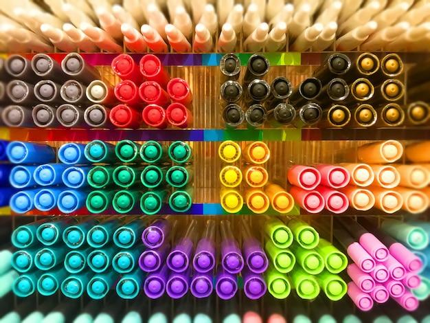 Canetas variadas com cores coloridas vistas do lado do boné