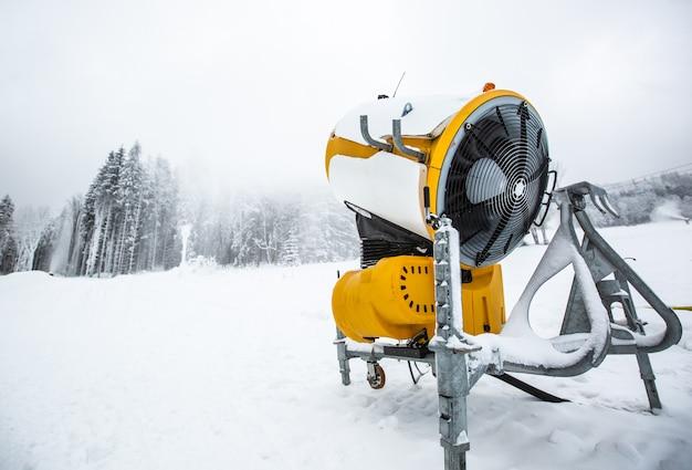 Canhão de neve, metralhadora ou arma nevando nas encostas ou montanha para esquiadores e snowboarders, neve artificial