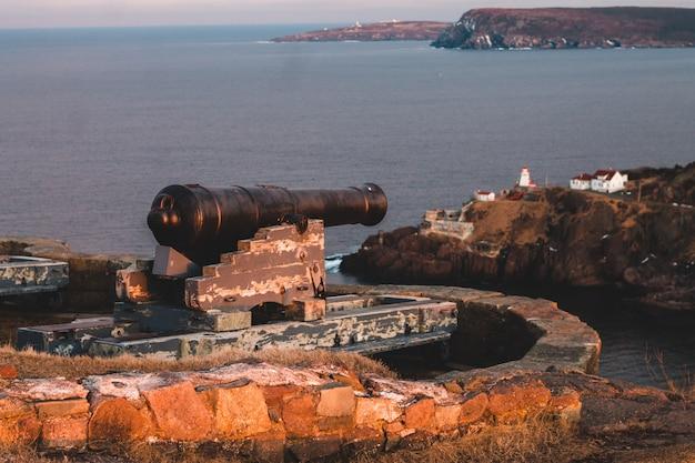 Canhão preto na rocha marrom perto do corpo de água durante o dia Foto gratuita