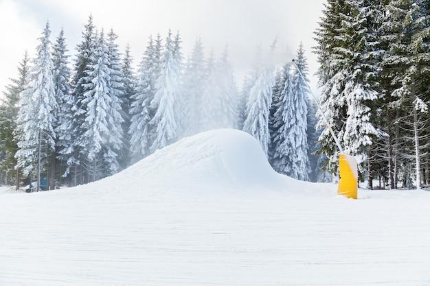 Canhões de neve da estação de esqui correndo na neve e nas árvores nas férias de inverno nas montanhas de esqui e snowboard