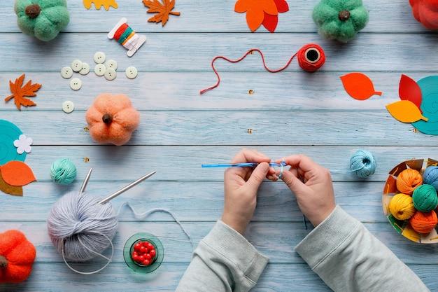 Canhoto em malha de crochê. vista superior da mesa de madeira com as mãos da canhota, bolas de lã, feixes de lã