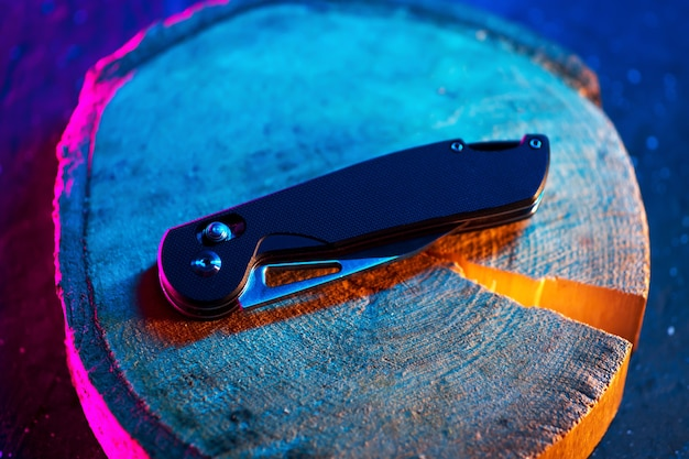 Canivete dobrável, moderno e de alta qualidade, vista de cima em um suporte de madeira. tendências de fundo de cor
