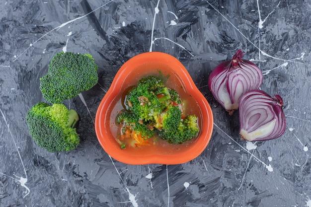 Canja de galinha, brócolis e cebola na superfície azul