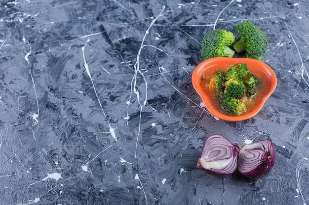 Canja de galinha, brócolis e cebola, sobre o fundo azul.