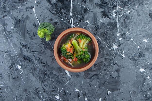 Canja de galinha caseira em uma tigela, na superfície de mármore.