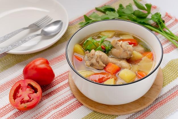 Canja de galinha com batata e ingredientes na mesa