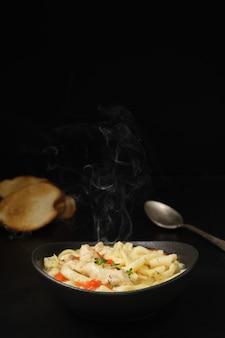 Canja de galinha com legumes, especiarias e macarrão caseiro em uma mesa escura.
