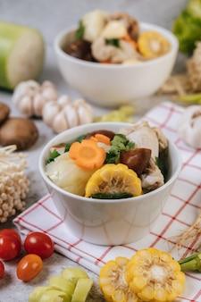 Canja de galinha com milho, cogumelo shiitake, cogumelo enoki e cenoura.