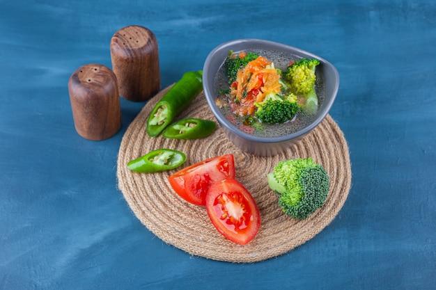 Canja de galinha em uma tigela e vegetais fatiados em um tripé na superfície azul
