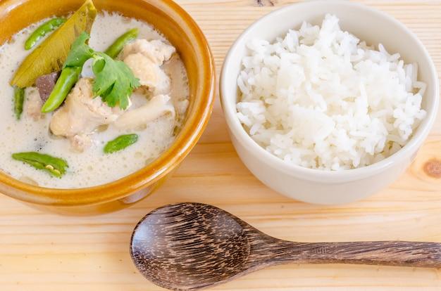 Canja de galinha tailandesa no leite de coco (tom kha gai) com arroz no fundo de madeira, alimento tailandês.