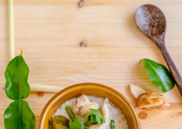 Canja de galinha tailandesa no leite de coco (tom kha gai) no fundo de madeira, alimento tailandês.
