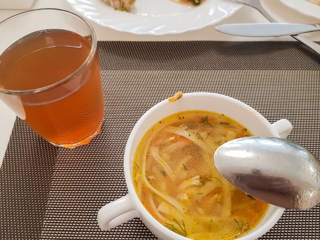 Canja de galinha tradicional servida em uma tigela branca com uma colher e um copo de compota, vista de cima, dieta saudável e balanceada