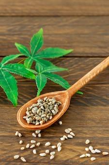 Cannabis cbd ou produtos de cânhamo - sementes de cânhamo e folhas verdes na mesa de madeira.