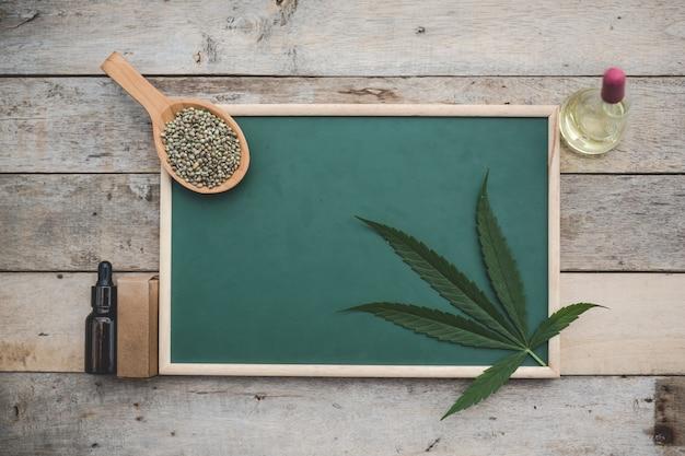Cannabis, sementes de maconha, folhas de maconha, colocadas na placa verde e há óleo de cânhamo ao lado no chão de madeira.