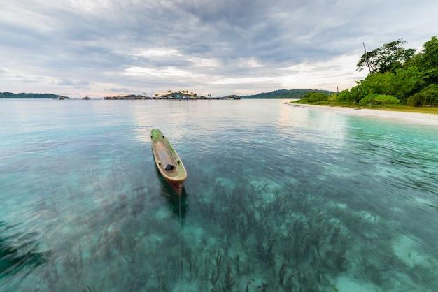 Canoa tradicional flutuando ao pôr do sol