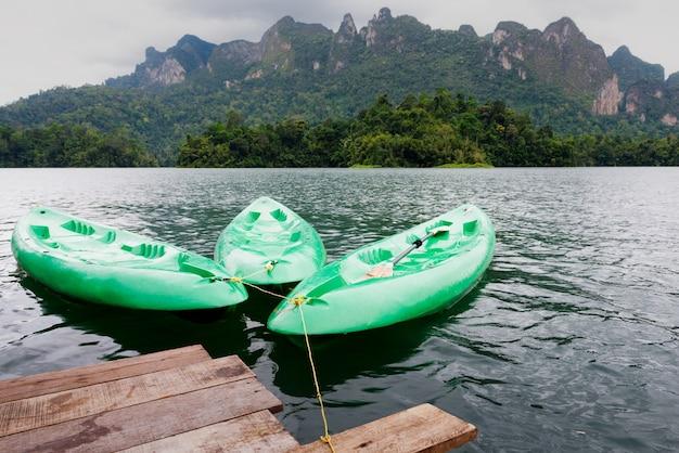 Canoa verde flutuando no lago da ásia e em casa