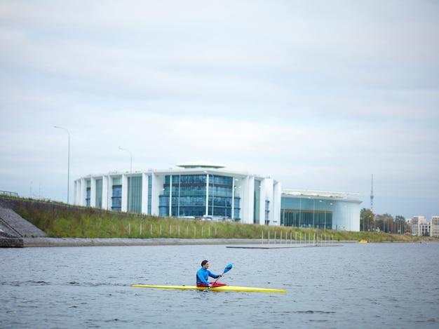 Canoagem urbana. jovem atleta do sexo masculino remando rio abaixo em uma canoa amarela