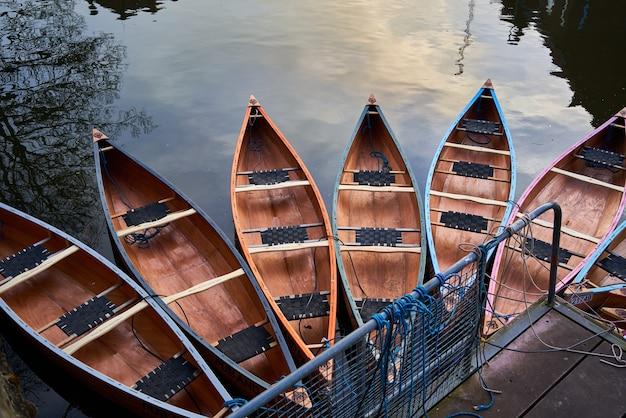 Canoas no rio perto de um cais em um parque sob a luz do sol
