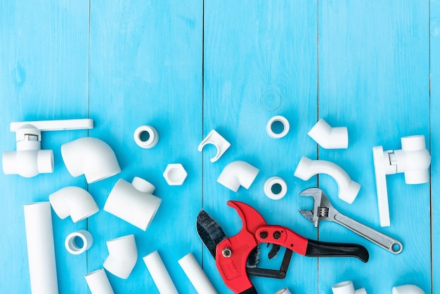 Canos plásticos para o sistema de água, ferramentas de corte de canos, chave, cantos, suportes, torneiras e adaptadores e em um fundo azul claro. copie o espaço. vista do topo.