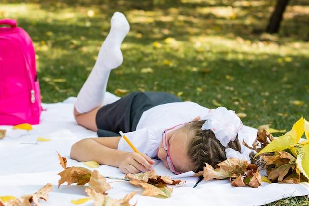 Cansada de dever de casa, uma estudante adormeceu em um cobertor em um parque ensolarado de outono. educação ao ar livre. conceito de volta às aulas