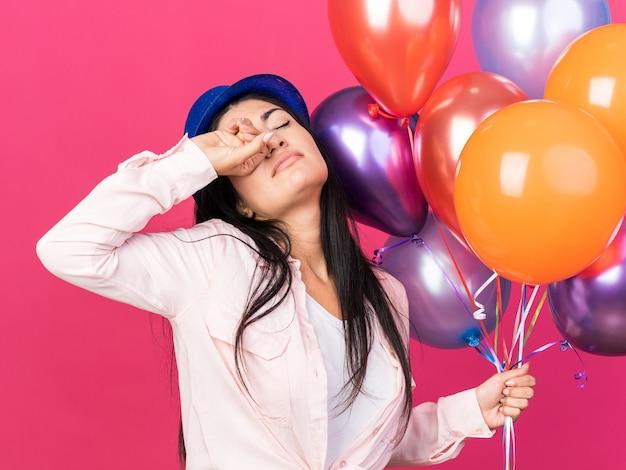 Cansada de olhos fechados, jovem mulher bonita usando chapéu de festa segurando balões, limpando os olhos com a mão isolada na parede rosa