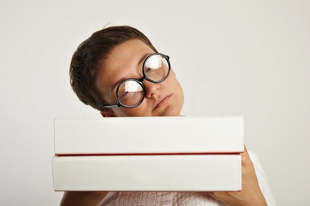 Cansada e linda aluna de óculos redondos dorme em seu plano educacional em duas pesadas pastas de documentos