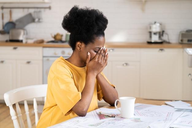 Cansada empresária africana freelance sofre de dor de cabeça, estresse trabalhando longe de casa exausta
