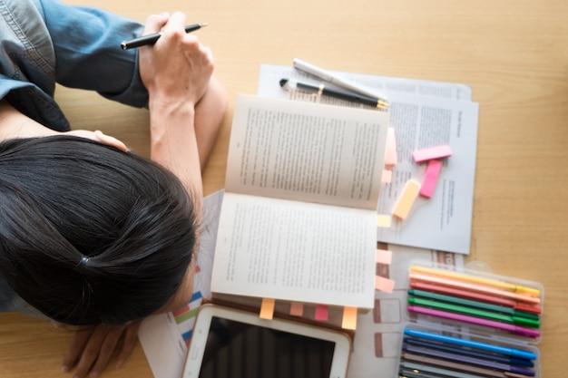 Cansada estudante, menina dormindo nos livros na biblioteca