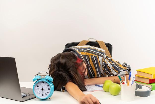 Cansada jovem estudante de óculos dormindo na mesa com ferramentas universitárias isoladas no fundo branco