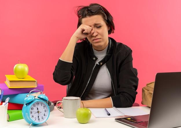 Cansada jovem estudante de óculos na cabeça, sentada na mesa com ferramentas da universidade, fazendo lição de casa, esfregando o olho isolado no fundo rosa
