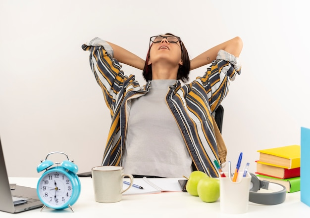 Cansada jovem estudante de óculos, sentada na mesa com as ferramentas da universidade, colocando as mãos atrás da cabeça com os olhos fechados, isolado no fundo branco