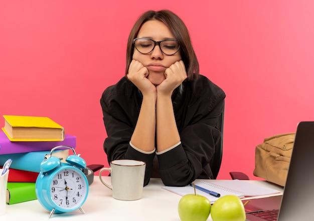 Cansada jovem estudante de óculos, sentada na mesa com as ferramentas da universidade, colocando as mãos embaixo do queixo com os olhos fechados, fazendo a lição de casa isolada no fundo rosa