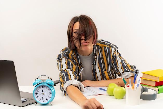 Cansada jovem estudante de óculos, sentada na mesa com ferramentas universitárias, olhando para a câmera, isolada no fundo branco