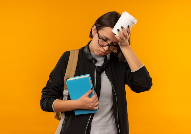 Cansada jovem estudante usando óculos e mochila segurando um livro tocando a cabeça com uma xícara de café com os olhos fechados, isolado em um fundo laranja