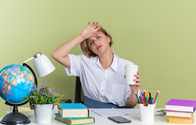 Cansada jovem loira estudante sentada na mesa com as ferramentas da escola, segurando a xícara de café de plástico, segurando a testa, olhando para a câmera isolada na parede verde oliva
