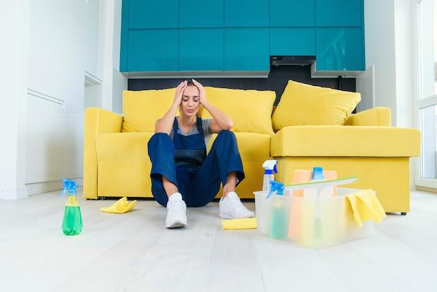 Cansada trabalhadora do serviço de limpeza, sentada perto do sofá e triste após lavar o chão na cozinha.