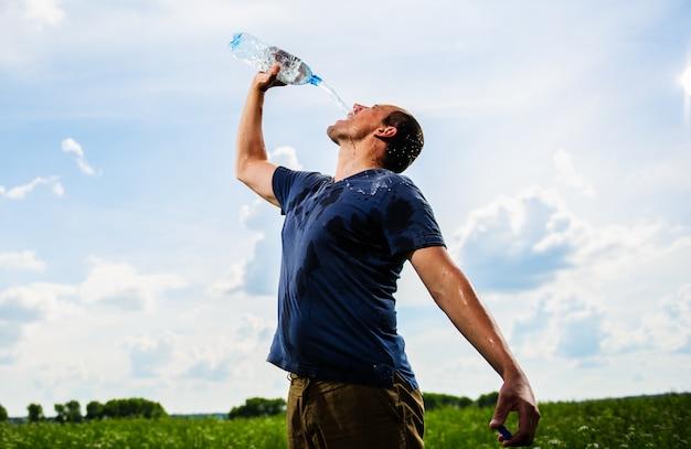 Cansado agricultor com sede está bebendo água no campo