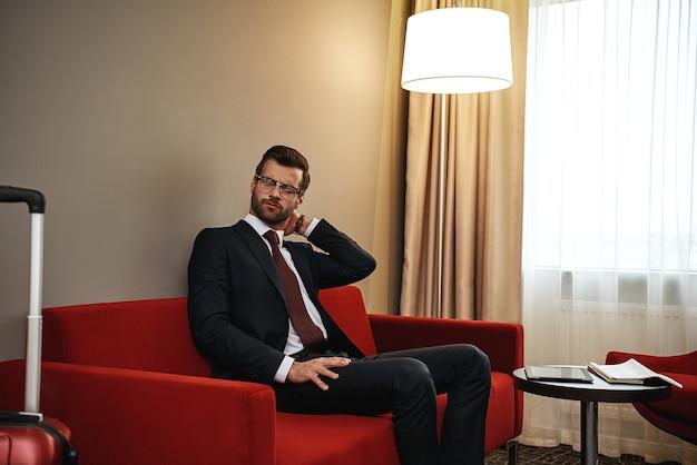 Cansado após uma viagem de negócios. homem de negócios com óculos está segurando o pescoço dele e sentado no sofá vermelho no quarto do hotel