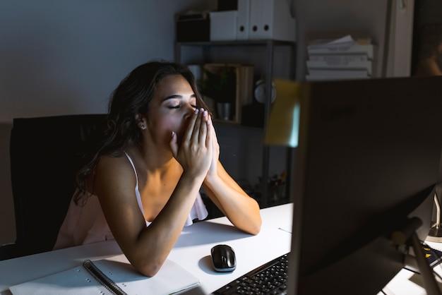 Cansado com sono mulher bocejando, trabalhando na mesa de escritório, excesso de trabalho e conceito de privação de sono