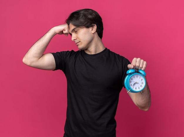 Cansado de olhos fechados, jovem bonito vestindo uma camiseta preta segurando um despertador e colocando o punho na testa isolada na parede rosa