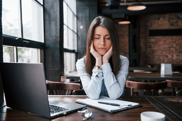 Cansado depois de tanto trabalho duro. mulher de negócios com roupas oficiais está dentro de casa no café durante o dia.