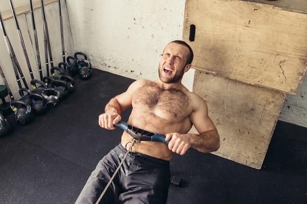 Cansado desportivos exercícios masculinos na máquina de exercício de força em um clube de ginástica