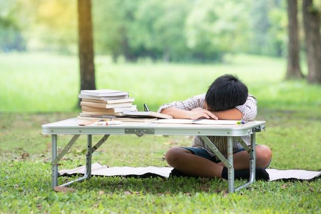 Cansado dormindo criança asiática enquanto lê o livro no parque