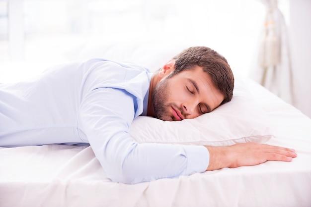 Cansado e com excesso de trabalho. jovem bonito com camisa dormindo na cama