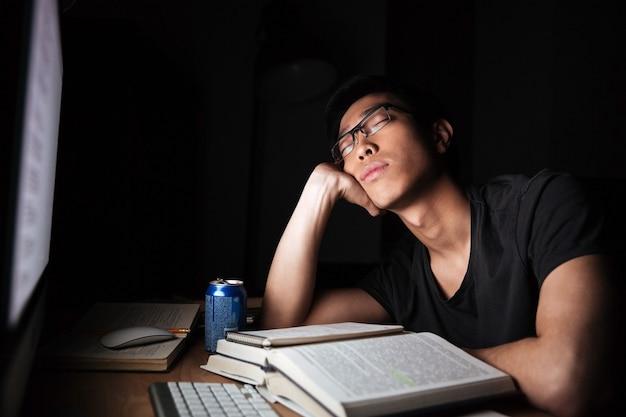 Cansado e exausto jovem asiático estudando e dormindo em frente ao computador à noite