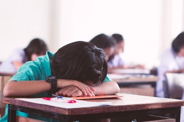 Cansado estudante uniforme dormindo em um teste de exame em sala de aula